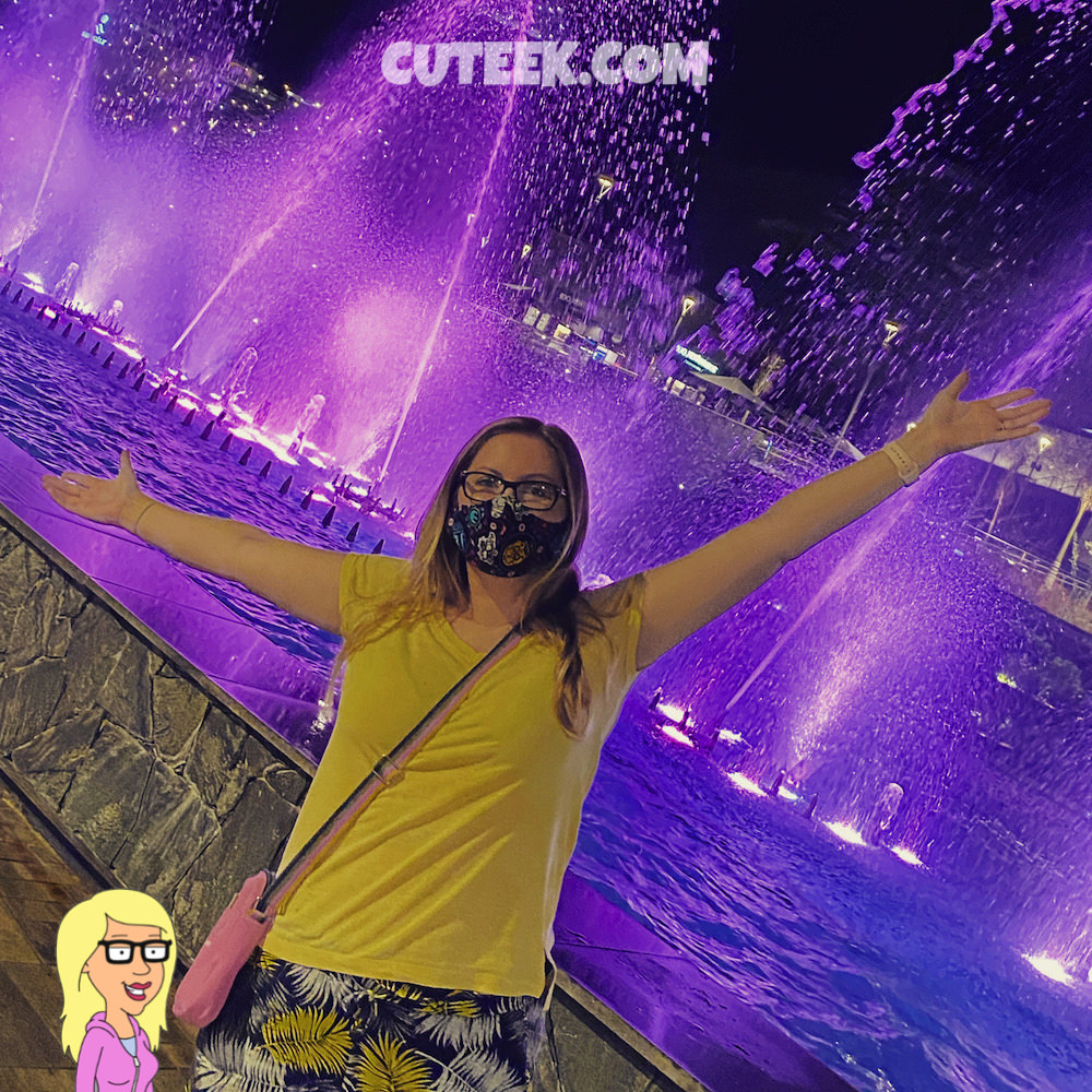 Geek Girl Standing in Front of a Purple Fountain