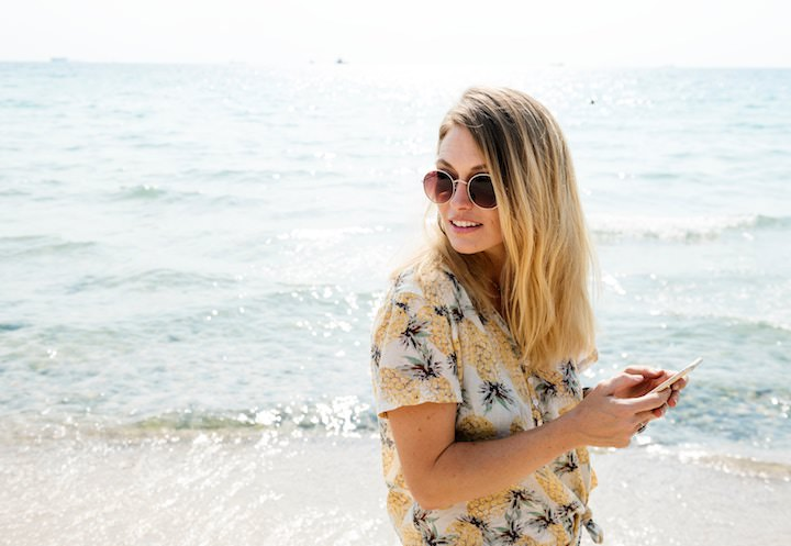 Girl at the beach checking social media after improving her social media strategy